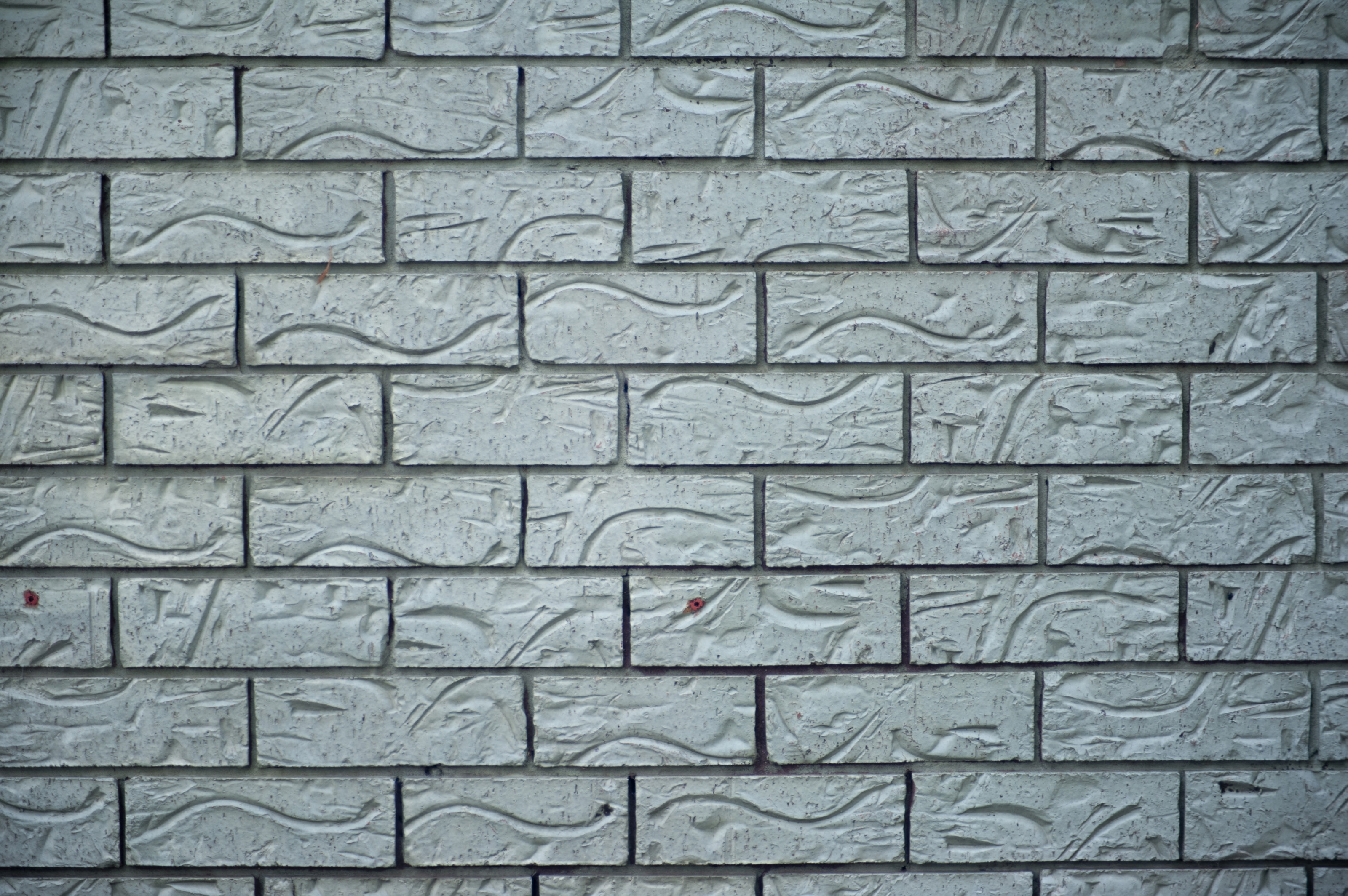 Background Texture Of Ornamental Grey Bricks With An Indented Decorative Pattern In A Full Frame