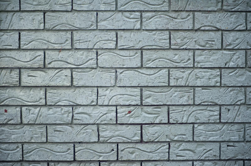 Background texture of ornamental grey bricks with an indented decorative pattern in a full frame background