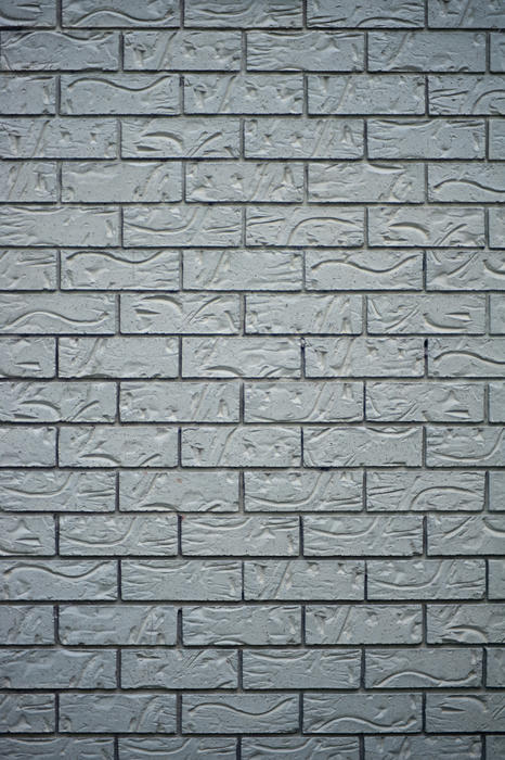 Architectural background texture of a grey brick wall with decorative patterned bricks in vertical format