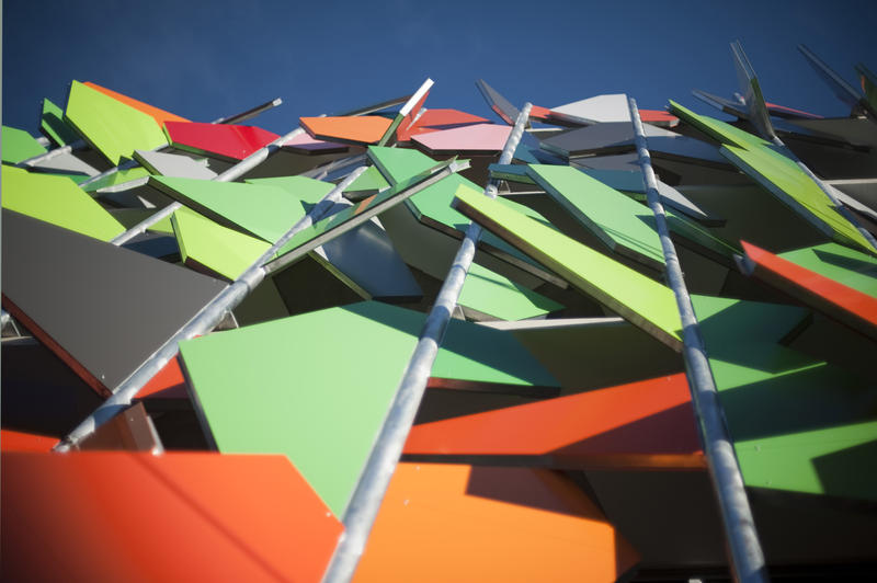 Modern colourful building facade in Melbourne adorned with multicoloured angular panels in random orientation, low angle view