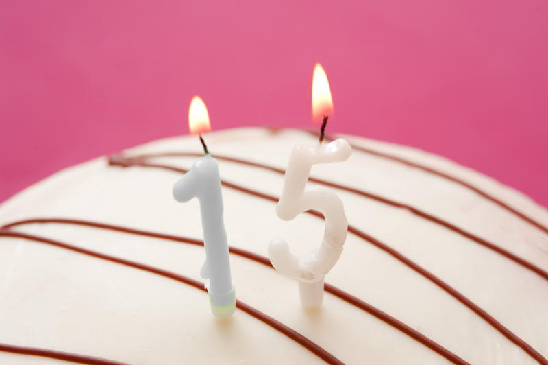 Close up White Candles on a Cake for 15th Birthday Celebration Against Pink Background.