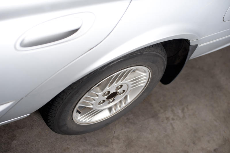 High angle view of the wheel and side door of a white car parked on asphalt