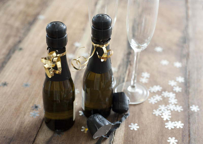 Two half bottles of champagne tied with golden bows alongside two elegant flutes to celebrate a romantic occasion or festive Christmas and New Year