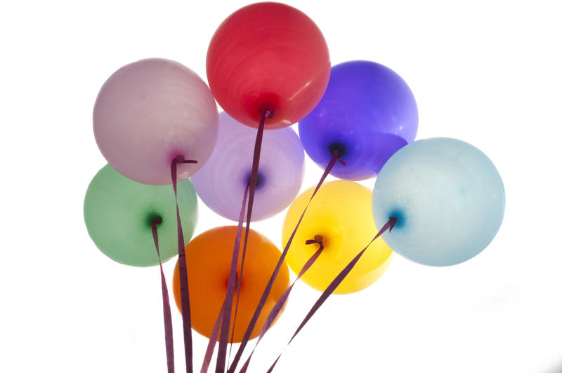 Bunch of colorful party balloons in the colors of the rainbow tied with ribbons floating in the air, isolated on white