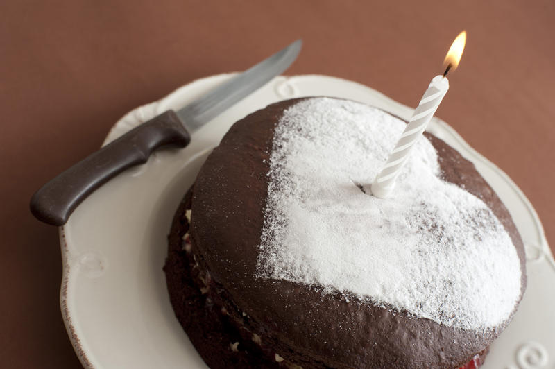 Close up Lighted Candle on Chocolate Cake, Decorated with Heart Shape Sugar on Top, Placed on a Plate with Knife on the Side.