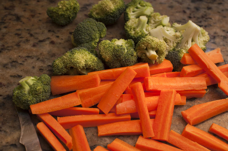 Chopped vegetables on a kitchen counter including carrot batons and broccoli pieces ready to be cooked as accompaniments to a meal