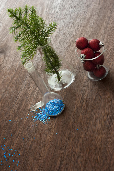 High Angle View Christmas Chemisty Concept Still Life - Small Evergreen Branch, Blue Glitter and Red Ornaments in Various Sized Glass Science Beakers on Textured Wooden Table with Copy Space