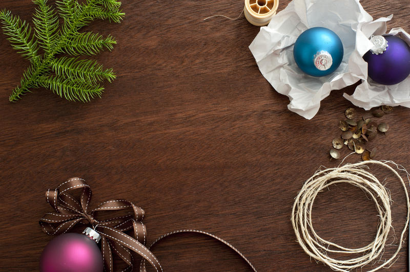 Christmas decoration components for decorating the house lying on a wooden desk with baubles, string, pine branch, and ribbon around central copyspace, overhead view