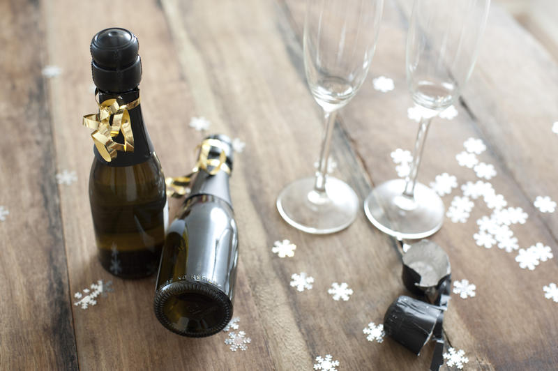 Two bottles of champagne decorated with Christmas ribbon with empty flutes alongside surrounded by scattered snowflake decorations conceptual of celebrating the festive season
