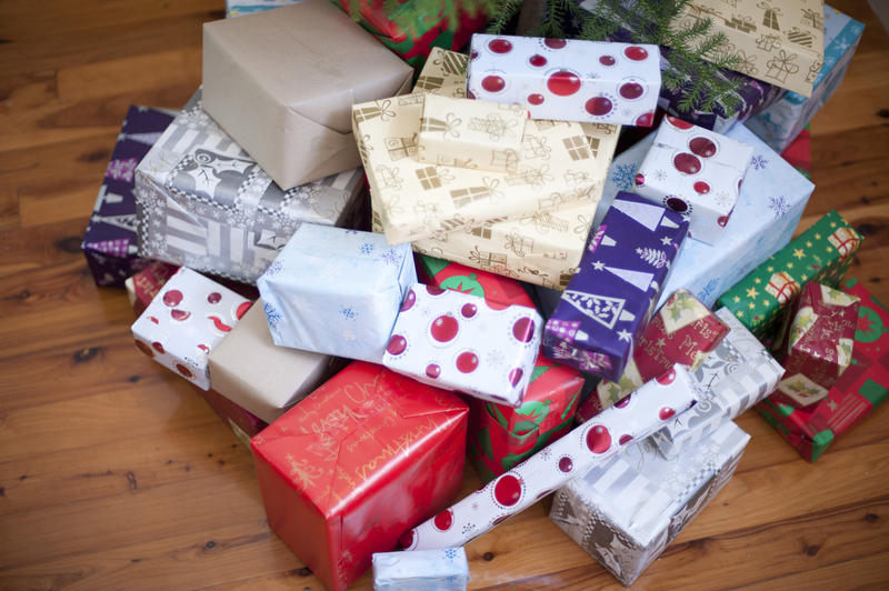 High angle view of a large pile of pretty colourful Christmas gifts in a variety of patterned gift wrap on a hardwood floor in a home