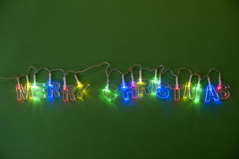 Colorful garland of Christmas lights in multiple colors sparkling on a dark green background, with copyspace above and below