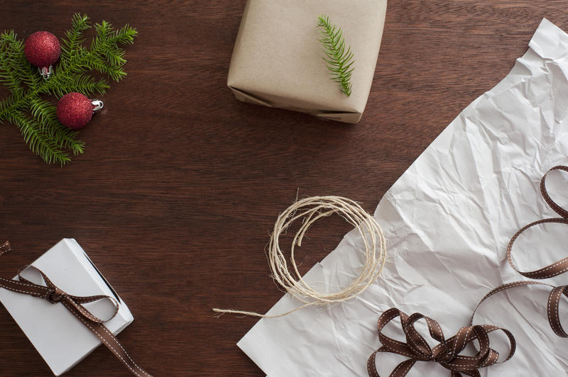 Preparations for Christmas with twine, ribbon, baubles , pine branch and gifts laid out on a table for gift wrapping and decorating, overhead view with copyspace