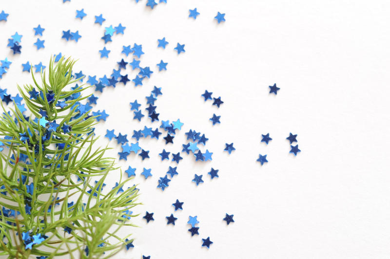 Christmas card background with a fir branch and colorful blue stars scattered across a white background with copyspace for your seasonal greeting