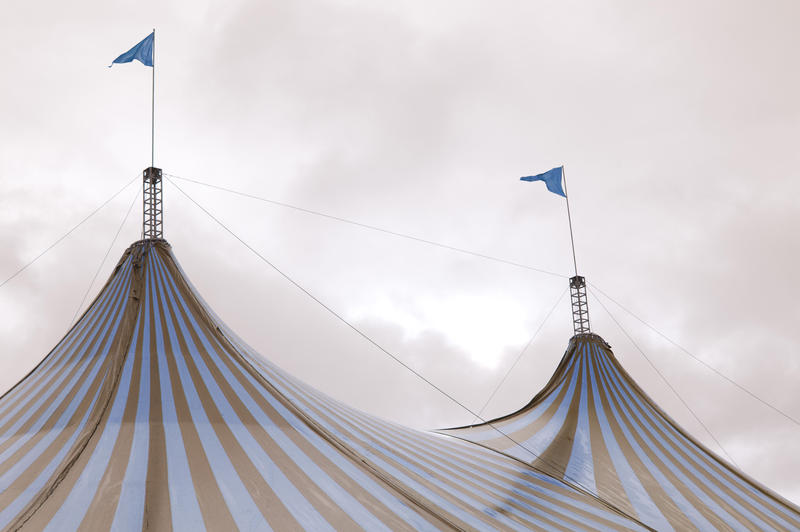 Colorful striped red and white Big Top tent at a circus flying two flags from the centre poles against a cloudy sky