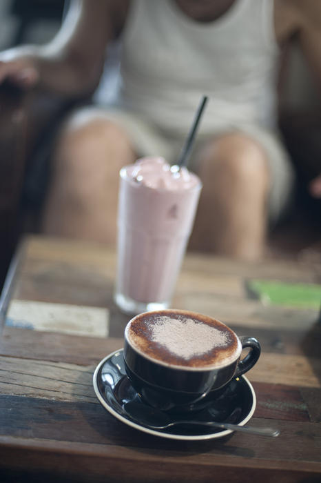 Cup of cappuccino and a milkshake on a table in a restaurant or cafeteria with a persons legs visible behind