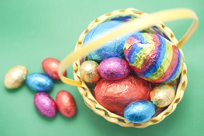A display of coloured Easter Egg in their foil wrapping in and alongside a wicker basket