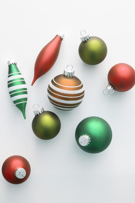 Colorful selection of Christmas ornaments scattered on a grey background with copy-space for your seasonal greeting