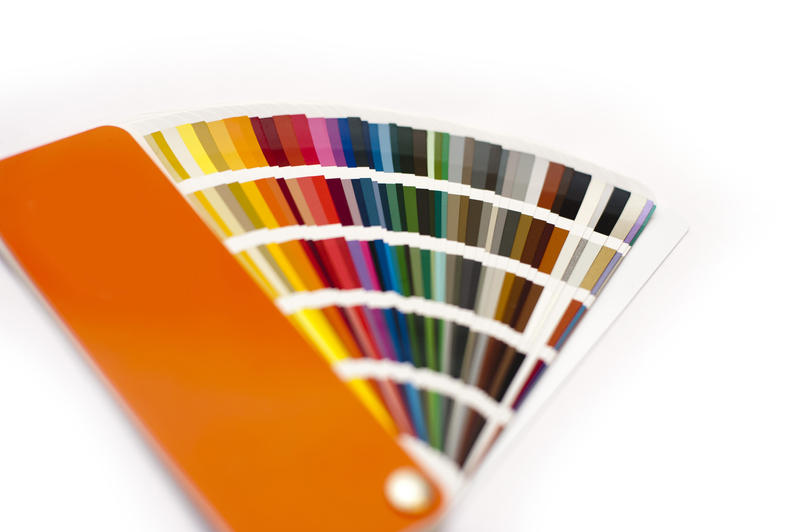 Opened color chart for painting or interior decorating fanned to show the colors of the spectrum in various hues and shades, on white