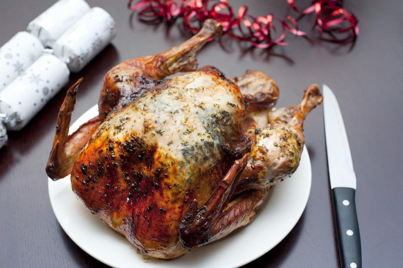 Whole roast Christmas turkey served ready on a plate for carving alongside festive crackers and table decorations