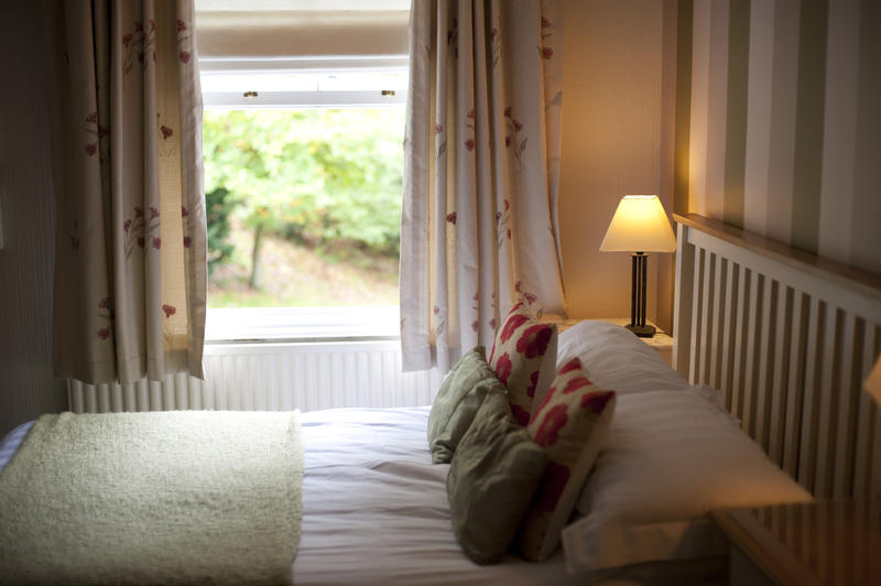 Country bedroom with a view over a comfortable double bed to a window overlooking a leafy green garden