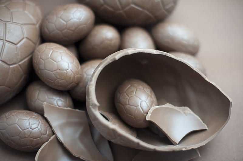 Cracked milk chocolate Easter egg accompanied by a collection of various sized eggs on a brown background