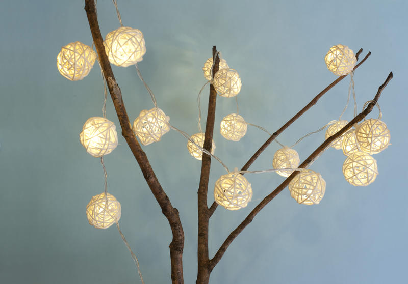 Decorated Christmas branch with shining rustic wicker lights over a blue grey background for a festive seasonal background
