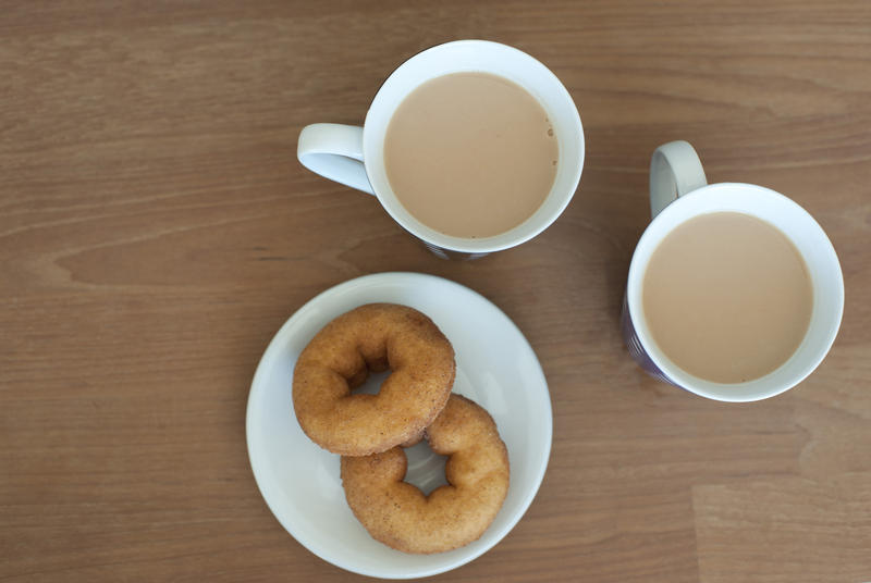 Aerial View of Cups of Creamy Coffee and Plate of Doughnuts on Side Served on Brown Wooden Table