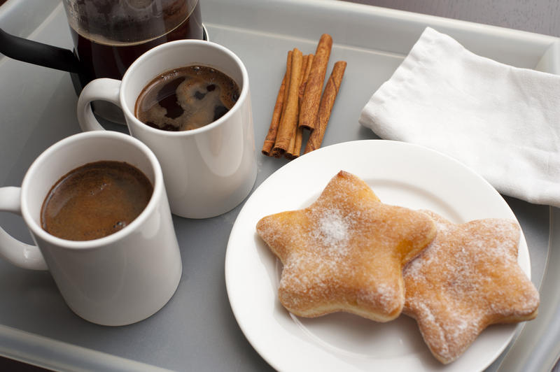 Breakfast on grey tray, two cookies, cinnamon and two cups of fresh hot coffee