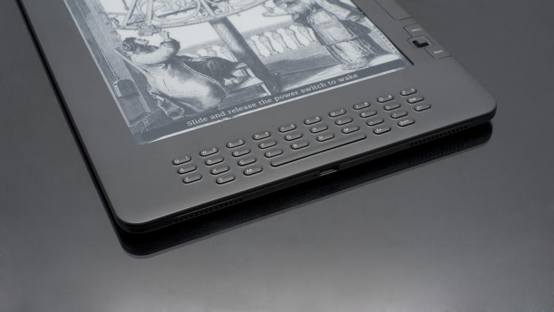 Close up High Tech Electronic Book Device on Top of Black Table, Emphasizing Copy Space.