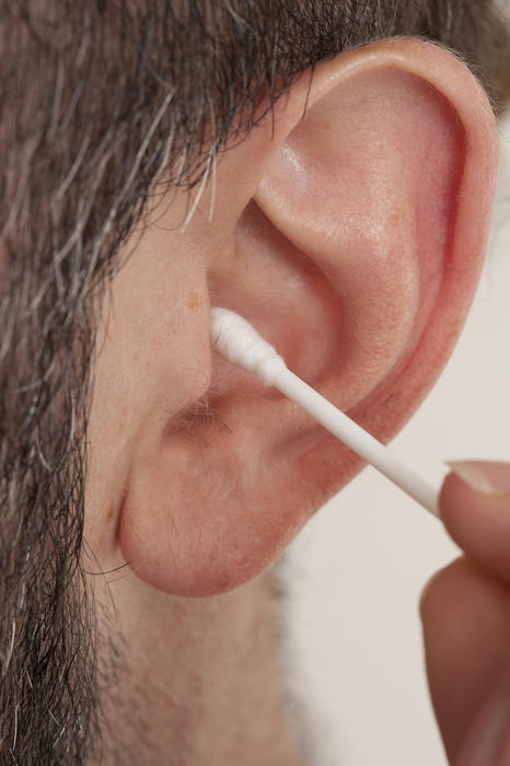Person de-waxing their ear using a cotton bud in a personal hygiene and healthcare concept, close up view