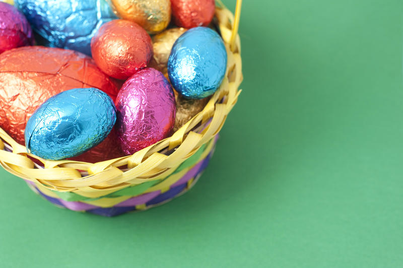 Easter Egg background with a basket filled with colourful foil wrapped eggs in one corner and copyspace on a green background