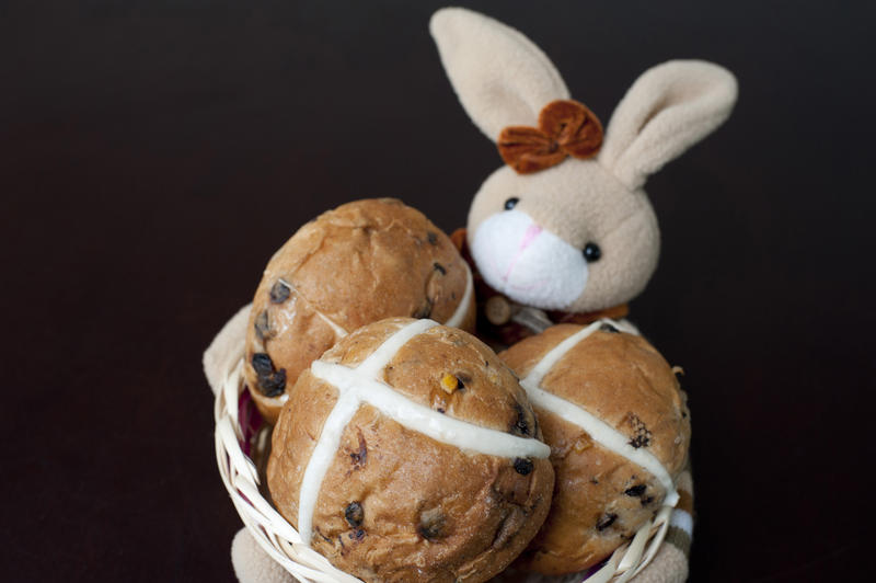 Cute little Easter bunny with traditional spicy fruity hot cross buns with a white cross commemorating the crucifixion of Christ
