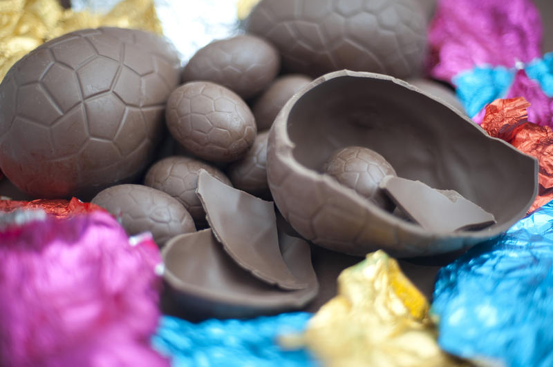 Easter Sunday treat with opened cracked and broken chocolate Easter eggs lying amongst their colourful foil wrappers