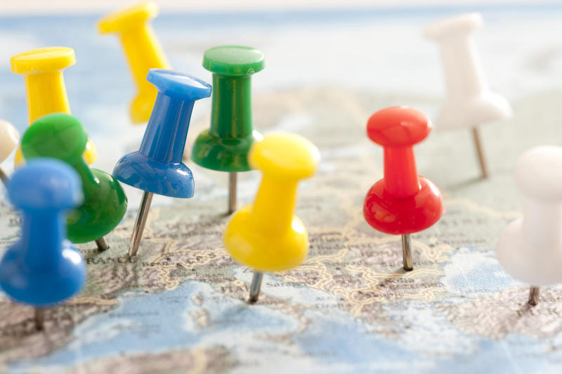 Close Up of Multi-Colored Thumb Tacks Inserted in Various Locations in Europe Map