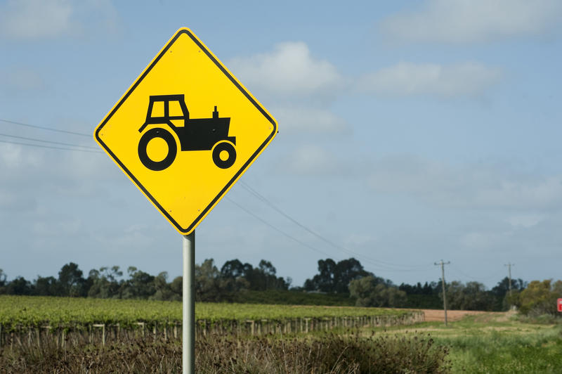 Close up Black and Yellow Traffic Farm Sign with Tractor Symbol In Front of a rural landscape