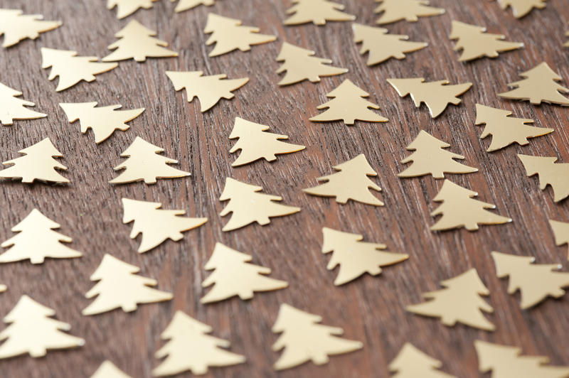 Festive background pattern of Christmas trees with gold tree decorations scattered randomly on a wooden surface view at a low angle