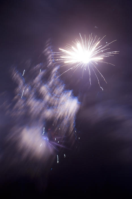 Fireworks display with wafting smoke as a bright white rockets bursts in a shower of fiery sparks in a night sky