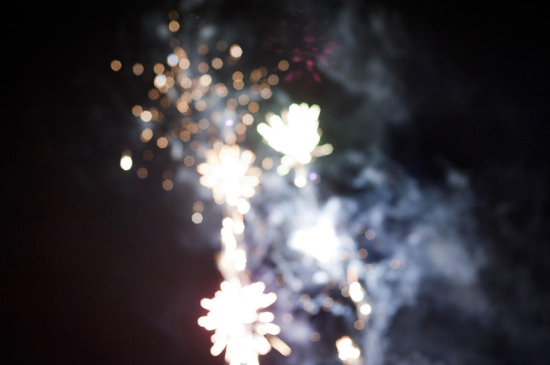 Festive bokeh of defocused bursting fireworks in a night sky during a holiday celebration with copyspace to the left side