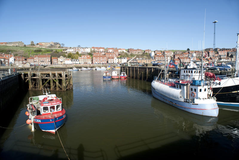 Upper harbour in Whitby with fishing boats and a trawler moored in the calm water