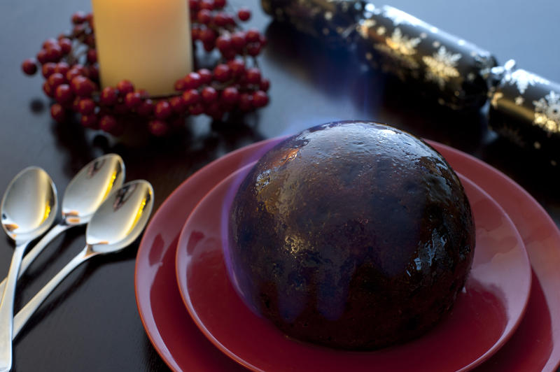 Flaming rich fruity steamed Christmas pudding doused in brandy and set alight served at the table