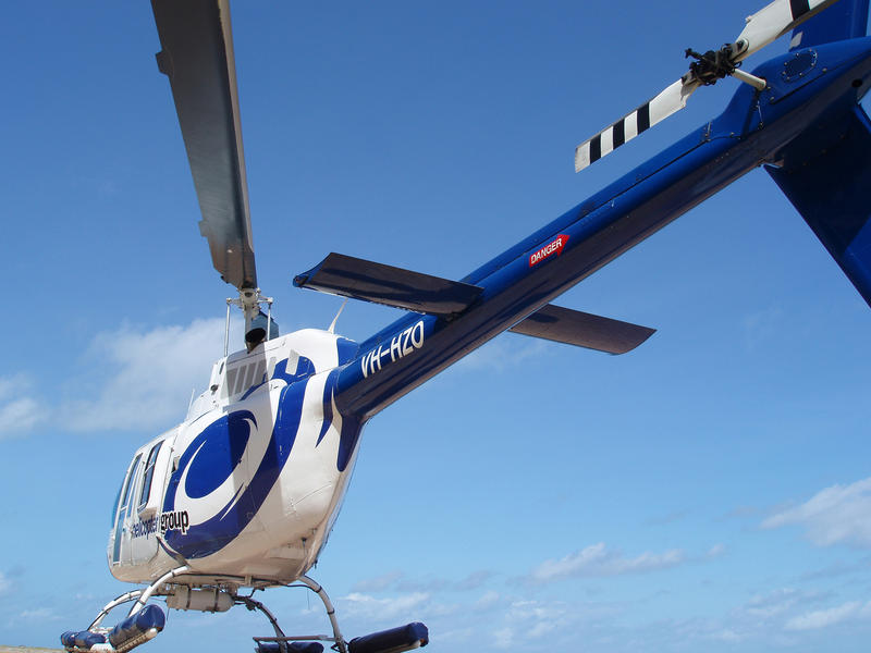 Low angle view of a blue and white helicopter parked on a helipad against a blue sky - no ground visible