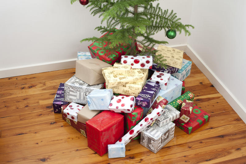 Pile of Christmas gifts st the base of a tree in different shapes and sizes wrapped in colourful wrapping paper with traditional patterns