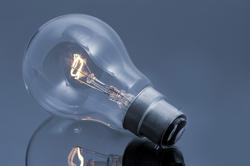 10757   Glowing Light Bulb on Glossy Gray Table