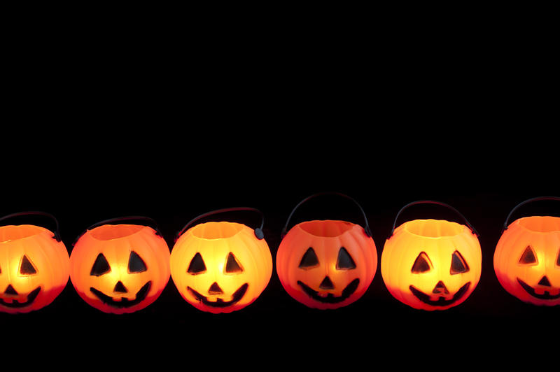 Line of Halloween pumpkin jack-o-lanterns glowing in the dark with plenty of copyspace above for your greeting or invitation