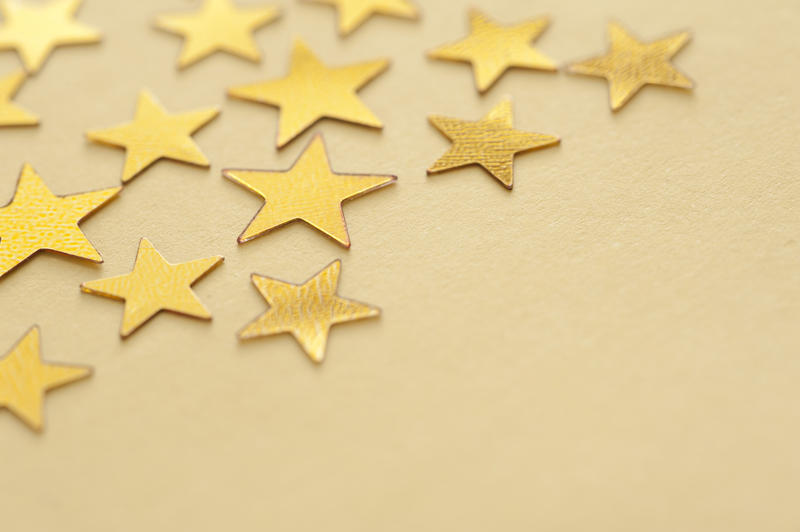 Gold star background with copyspace for your festive or Christmas greeting viewed at an oblique angle scattered on a yellow background