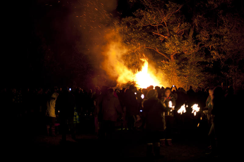 Crowd standing grouped in a field at night watching a roaring bonfire on Guy Fawkes with fiery orange flames leaping into the air - not model released
