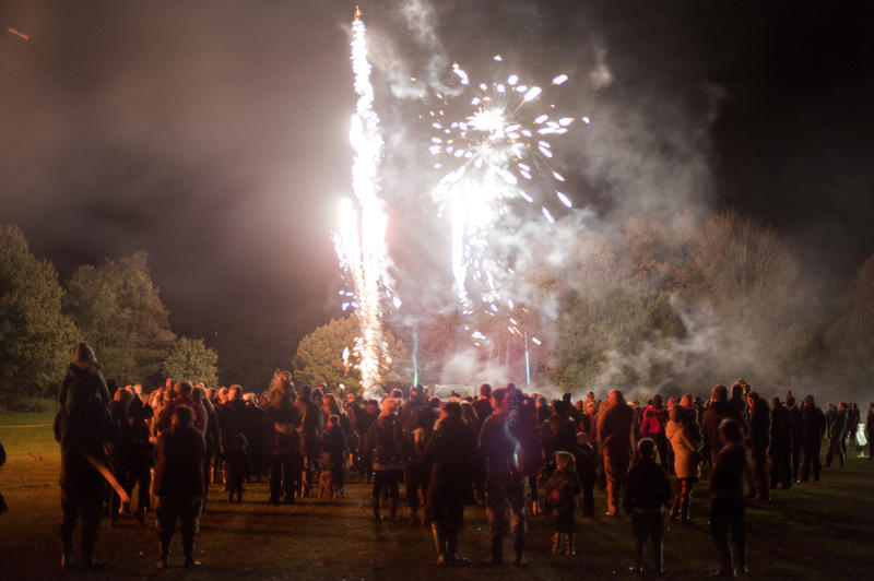 Crowd of people watching a fireworks display in an outdoor field as colorful exploding rockets light up the night sky during a Bonfire Night or Guy Fawkes celebration