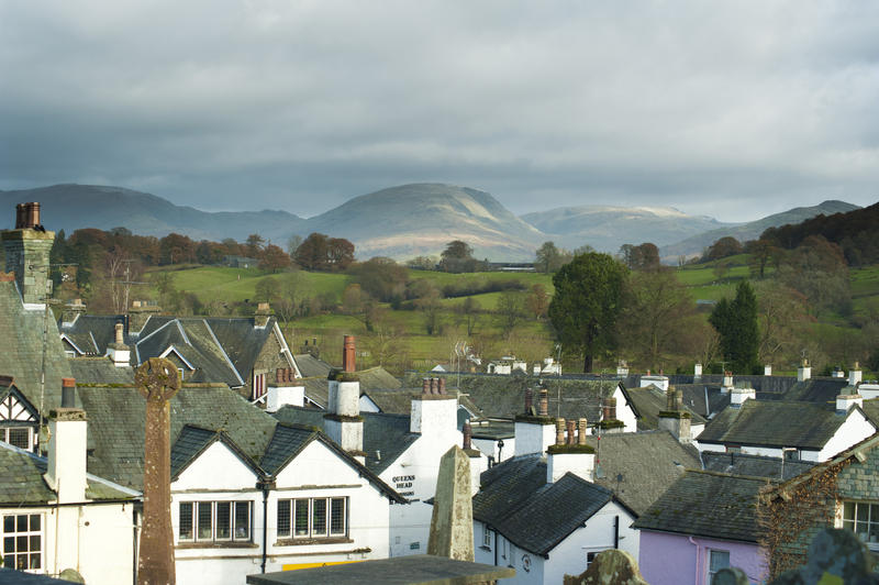 Hawkshead roofscape with a view across the quaint traditional whitewashed cottages to the scenic countryside of the Cumbrian Lake District beyond