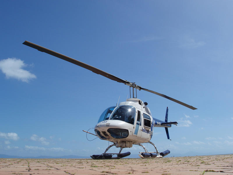 Helicopter parked on a helipad against a sunny blue sky with the rotor blade forming a diagonal line through the frame