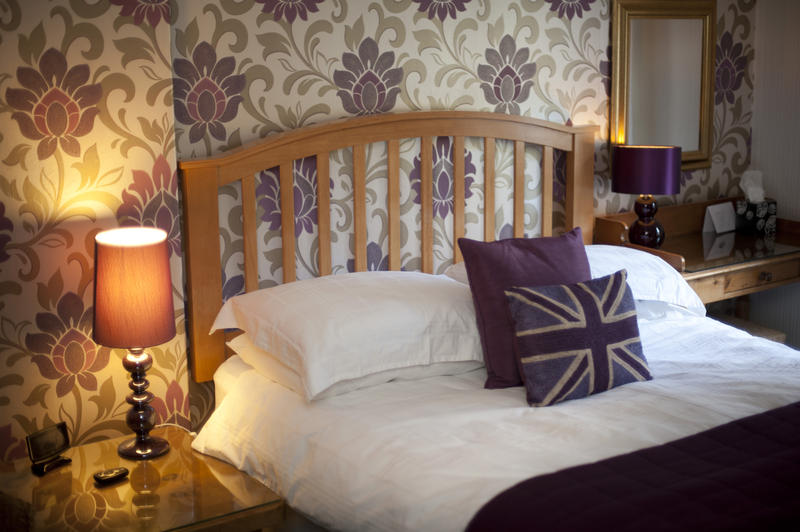 Patriotic British bed with Union Jack cushions in a homely bedroom with floral wallpaper